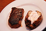 A baked potato with butter lays on a white plate with a piece of sirloin steak.