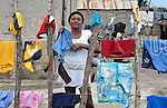 A woman hangs laundry to dry on a fence in Batey Bombita, a community in the southwest of the Dominican Republic whose population is composed of Haitian immigrants and their descendents.