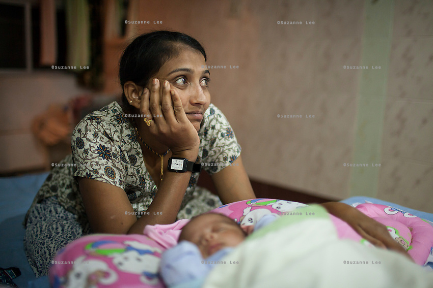 Nita, an ex-surrogate, has continued to work with Dr. Patel's Akanksha clinic by selling her breast milk to other surrogacy clients, and as a nanny for new-born test tube babies, like these twins in the Neonatal Intensive Care Unit (NICU) at the Apara Nursing Home, where babies from the Akanksha clnic are often sent for neonatal and other post-birth intensive care, in Anand, Gujarat, India on 10th December 2012. Photo by Suzanne Lee / Marie-Claire France