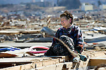 Fujiko Sato, 82, sits on the flattened remains of her  home in Rikuzentakata, Iwate Prefecture, Japan on  5 April 20011..Photographer: Robert Gilhooly