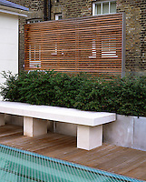 A limestone bench on the roof terrace is flanked by young Yew hedges growing in metal containers backed by a freestanding slatted wooden screen