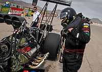 Mar 29, 2014; Las Vegas, NV, USA; NHRA top fuel driver Scott Palmer looks at oil on his engine during qualifying for the Summitracing.com Nationals at The Strip at Las Vegas Motor Speedway. Mandatory Credit: Mark J. Rebilas-USA TODAY Sports