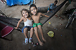 Two children swing in a hammock on the La Lempira Cooperative, near Ceibita, Honduras. La Lempira is an agricultural project which has been seized by armed peasants who claim the land is rightfully theirs under the country's agrarian reform law.