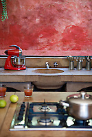 The kitchen worktops are all made of stone and the colour scheme is neutral save for this one vibrant red wall