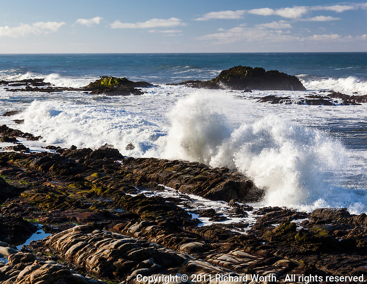 Waves send spray skyward as the crash against the rocky California coast.