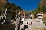 Yoshifumi Yamada, 84, chairman of Lake Shouji Touism Association, walks through a cemetery in which the remains of unidentifiable suicide victims are interred   near Aokigahara Jukai, better known as the Mt. Fuji suicide forest, which is located at the base of Japan's famed mountain west of Tokyo, Japan on 03 Nov. 2009. The local community built a hall, the red-roofed white building in the background of the photo, especially for the suicide victims to be interred.