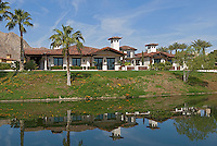View across lake of large Spanish style residence