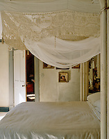 All the textiles and furniture in this feminine bedroom are in various shades of white that work together harmoniously