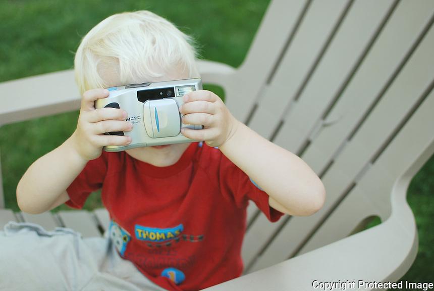 Little boy using old school digital camera