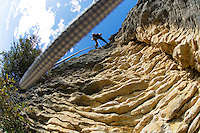 Rock climber rappelling down cliff