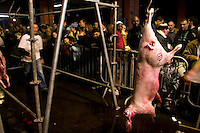 People watch the carcass of a freshly slaughtered sheep hang on a rack during the ritual sheep slaughter held for the Muslim celebration of Aid-el-Kebir at a temporary slaughterhouse set up in an hanger in Pantin, outside Paris, France, 1 February 2004. Photo Credit: David Brabyn.