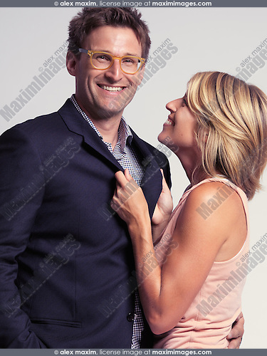 Smiling fashionably dressed couple. Isolated on gray background