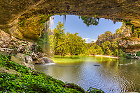 Hamilton Pool is located off of hwy 71 in Travis county about a thirty minute drive from Austin,Texas. The is a natural pool created by an underground river that collasped and formed by erosion over  thousand years.  The erosion created this cave with stalactite growing from the celling, a waterfall flowing over the limestone along bolders along with moss along with emerald green swimming hole.  The preserve includes about 232 acres of natural habitat and is home to the golden cheek warble.   This place draws a lot of people want to enjoy this place on a hot summer days but if you want to come be sure and call ahead and make reservation.  Over the years the place has been loved to death and you now need a reservation just to get in also it is also good to make sure it is open for swimming because it is a natural swimming hole no chemicals are added to the water so at times it get shut down due to high bateria counts.  This nature preserver is part  of the  Balcones Canyonlands Preserve and is a protected environment.