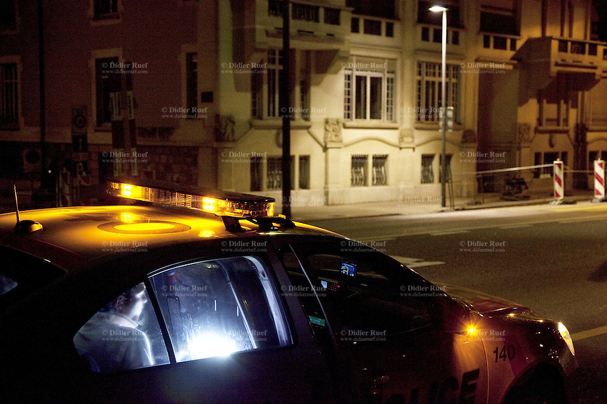 """Switzerland. Geneva. A convict man seats in a police car on duty, parked on the Quai du Mont-Blanc, during the night. The inmate is a Gypsy man from France. The Romani people are also known by a variety of other names, in English as Gypsies and Roma, in Central and Eastern Europe as Tsigani. French Romani people are generally known in spoken French as """"Manouches"""" or """"Tsiganes"""". """"Romanichels"""" or """"Gitans"""" are considered pejorative and """"Bohémiens"""" is outdated. 1.04.12 © 2012 Didier Ruef"""