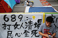 Pro-democracy protesters pass the time in their encampment in the part of Hong Kong's financial central district they are occupying October 31, 2014. The former British colony of Hong Kong, which returned to Chinese rule in 1997, has witnessed a month of protests calling on the Beijing-backed government to keep its promise of introducing universal suffrage. The protests have for the most part been peaceful, with occasional clashes between the student-led protesters and Beijing supporters seeking to move them from the streets.   REUTERS/Damir Sagolj (CHINA)