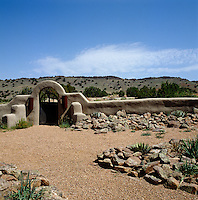 A door in a basalt dyke built from lava covered in stucco leads to the wild prairie beyond