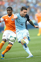 Claudio Bieler (16) forward Sporting KC holds off Kofi Sarkodie (8) defender Houston Dynamo to shoot on goal..Sporting Kansas City and Houston Dynamo played to a 1-1 tie at Sporting Park, Kansas City, Kansas.