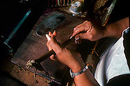 Cuba, March 1992: Steps involved in rolling a cigar. Rolling the external leaf of a cigar around the 'heart', In La Corona, The largest Cigar factory in Havana.
