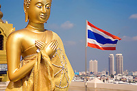 Thailand. Bangkok. Wat Saket, Golden Mount temple. Buddhist temple. On the temple's roof, a giant golden statue of Buddha. View on the city and the rooftops of Bangkok with modern and new highrise buildings. A thai flag floats in the air. The flag of the Kingdom of Thailand shows five horizontal stripes in the colours red, white, blue, white and red, with the middle blue stripe being twice as wide as each of the other four. The three colours red-white-blue stand for nation-religion-king, an unofficial motto of Thailand. The flag was adopted on 28 September 1917, according to the royal decree. 28.03.09  © 2009 Didier Ruef