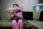 16/07/2014. Sulaymaniah, Iraq. With a picture of the Patriotic Union of Kurdistan (PUK) leader, and Iraqi President, Jalal Talbani in the background, female peshmerga Paxshan Omer adjusts the stock of her Kalashnikov assault rifle in the family home in Sulaymaniah. As well as being a single mother, her husband having died of illness in 2000, Paxshan is also one of 500 female peshmerga fighters who are based at the Farmanday peshmerga base near Sulaymaniah in Iraqi-Kurdistan.