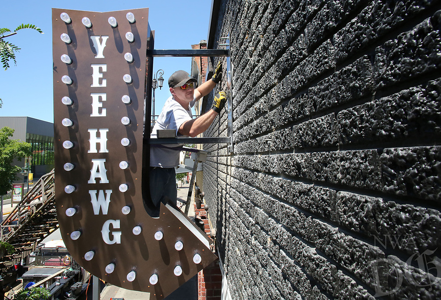NWA Democrat-Gazette/DAVID GOTTSCHALK  Nathan Bingham, with Arkansas Sign and Banner of Bentonville, places concrete anchors Tuesday, May 16, 2017, on the base of a new sign on Dickson Street in Fayetteville. Bingham was working with Mike Payne on the light emitting diode sign over the new establishment Yee Hawg.