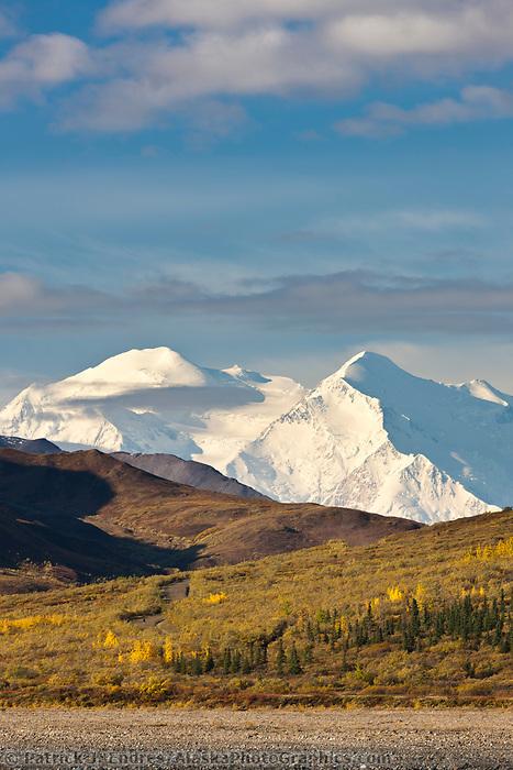 The north and south summits of Denali are visible as a bus travels the gravel, Denali Park road, Denali National Park.