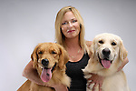 Portrait of a Woman hugging two one year old Golden Retrievers. Isolated on gray background. Gray Valley Kennels - Toronto.