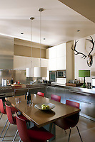 The contemporary kitchen in brushed steel is furnished with a custom-made table and chairs from Habitat