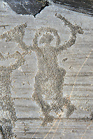 Petroglyph, rock carving, of a warriors with a helmet, small round shield and sword. Carved by the ancient Camunni people in the iron age between 1000-1200 BC. Rock no 24, Foppi di Nadro, Riserva Naturale Incisioni Rupestri di Ceto, Cimbergo e Paspardo, Capo di Ponti, Valcamonica (Val Camonica), Lombardy plain, Italy
