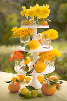 A colourful arrangement of garden flowers and citrus fruit on a three-tiered cake stand