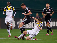 Perry Kitchen (23) of D.C. United is tackled by Wil Trapp (20) of the Columbus Crew during a MLS game at RFK Stadium in Washington, DC.  D.C. United lost to the Columbus Crew, 3-0.
