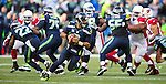 Seattle Seahawks quarterback Russell Wilson rolls out to pass against the Arizona Cardinals at CenturyLink Field in Seattle, Washington on November 23, 2014. Wilson completed 17 of 22 passes for 211 yards, rushed for 73 yards and threw one touchdown in  the Seahawks 19-3 win over  the Cardinals.   ©2014. Jim Bryant Photo. All Rights Reserved.