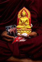 A monk holds an icon of Buddha and a photograph of himself with opposition leader Aung San Suu Kyi, on a protest march led by Buddhist monks calling for the overthrow of the country's military junta.
