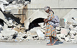 A woman walks past a collapsed building in Port-au-Prince, Haiti, which was devastated by a January 12 earthquake.