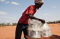 Kenya - Dadaab - A Somali man selling cooking pots to refugees who have just arrived at the camp.