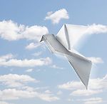 Origami Peace dove made from folded paper Symbol of love and peace Isolated with a clipping path on blue sky background