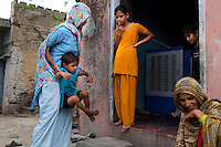 Nafeesa (left, in blue), 27, tends to her 4 children in her house in a slum in Tonk, Rajasthan, India, on 19th June 2012. Nafeesa's health deteriorated from bad birth spacing and over-working. While her husband works far from home, she rolls bidis (indian cigarettes) to make an income and support the family. She single-handedly runs the household and this has taken a toll on her health and financial insufficiencies has affected her children's health. Photo by Suzanne Lee for Save The Children UK