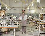 At a garment factory in the SITE industrial area of Karachi.  A scene from the sewing and stitching work floor where the various pre-cut pieces of clothing are put together into the complete product. Most all the people working on the floor are on short-term contracts only.