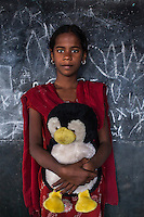 Tammanna, 8, poses for a portrait with a soft toy in the Guria Non-Formal Education center in the middle of the Shivdaspur red light district, Varanasi, Uttar Pradesh, India on 20 November 2013. Guria uses the soft toys as a form of therapy for the children of the women in prostitution and also use it as signals of the children's emotional wellbeing.
