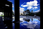 A day after rain, a pedestrian, far left, makes hiw way past columns and puddles as the reflection of clouds accompanies him as he makes his way along the plaza entrance to the Orange County Superior Courthouse, Thursday afternoon in Santa Ana.