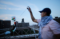 New York City, NY. 20 August 2014. A man holds balloons with the a Palestinian flag colors as he takes part during a Pro-palestine Rally across de Brooklyn Bridge in Manhattan.  Photo by Kena Betancur/VIEWpress