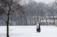 Two people walking in the snow in the White Rock Lake area in Dallas, Texas during a rare winter snowfall in February 2010.