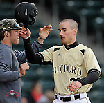 Josh Hyman of the Wofford Terriers is congratulated after scoring a run in a game against the Presbyterian Blue Hose on Wednesday, March 19, 2014, at Fluor Field at the West End in Greenville, South Carolina. (Tom Priddy/Four Seam Images)