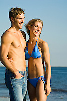 couple on the beach smiling at something off camera at the beach in Coney Island, NY