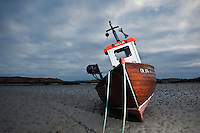 Fishing boat sits on habour sand at low tide, Ludag, South Uist, Outer Hebrides, Scotland