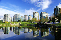 Reflection of condominium towers in pond, at entrance to Stanley Park, beside Coal Harbor, Vancouver, BC.