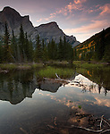 Mount Kidd and clouds are reflected in a small pond in the Kananaskis country area of Alberta, Canada.