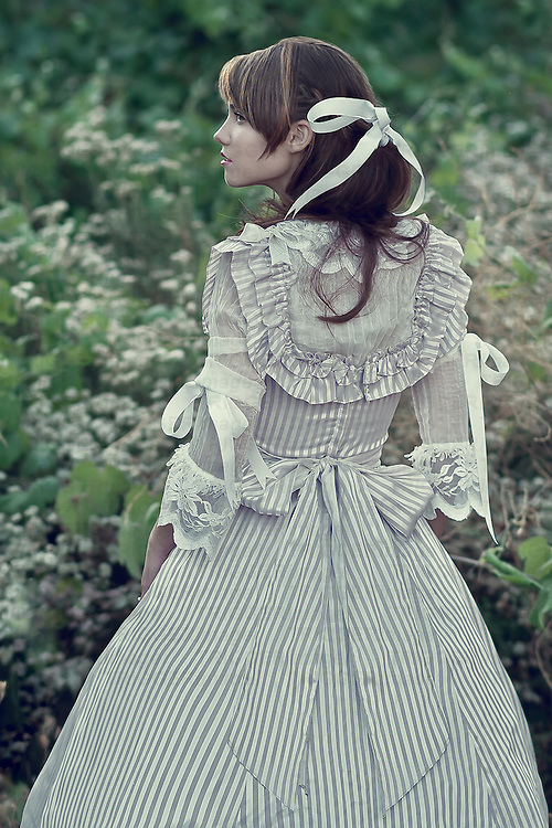 A young adult female wearing a vintage dress in a garden.