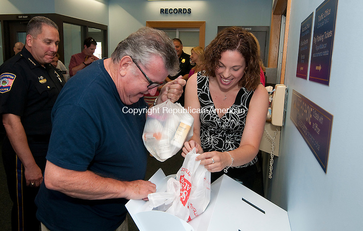 TORRINGTON, CT-080714JS07- Torrington resident Frank Stolfi gets a hand from Jessica Wright, Director of Prevention at the McCall Foundation, as he brought in prescription drugs to drop off in the new drop box during a press conference to dedication the box inside the lobby of the Torrington Police Department on Thursday. The box was made possible through efforts from the police department, The McCall Foundation, the Torrington Coalition to reduce youth substance use and the Litchfield County Opioid Taskforce. <br /> Jim Shannon Republican-American