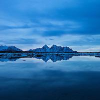 Reflection of Vågakallen mountain peak over coastline, Vestvågøy, Lofoten Islands, Norway